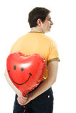 Young man holding a red heart shaped balloon Stock Image