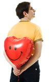 Young man holding a red heart shaped balloon Royalty Free Stock Photo