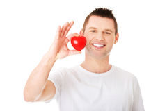 Young man holding a red heart Stock Photography