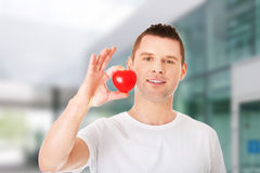 Young man holding a red heart Royalty Free Stock Image