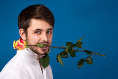 Young man holding a red rose in his mouth Stock Images