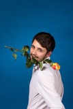 Young man holding a red rose in his mouth Stock Photo