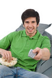 Young man holding remote control watch television Royalty Free Stock Photos
