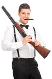 Young man holding a rifle and smoking cigar Royalty Free Stock Images