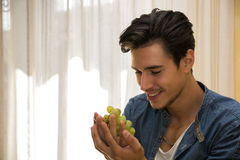 Young man holding a ripe bunch of grapes Stock Image