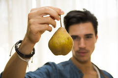 Young man holding a ripe yellow pear Stock Image