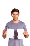 Young man holding ripped paper. On white background Stock Images
