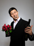 Young man holding rose flower and vine bottle Stock Images