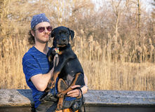Young man holding rottweiler puppy royalty free stock photography