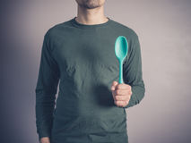 Young man holding a rubber spoon Royalty Free Stock Photo