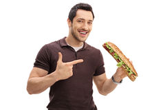 Young man holding a sandwich and pointing Royalty Free Stock Image