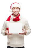 Young man holding in santa hat sign. Young casual caucasian man in red santa hat holding sign with nice toothy smile royalty free stock photography