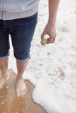 Young man holding a seashell, high angle view Royalty Free Stock Photo