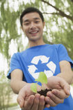 Young Man Holding Seedling in his Hands, Recycling Symbol, Low Angle View Stock Photo