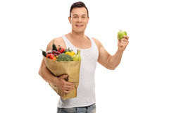 Young man holding a shopping bag and an apple Royalty Free Stock Image
