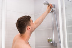Young man holding shower head with flowing water Royalty Free Stock Photography