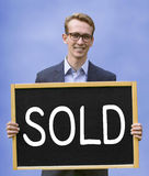 Young man holding sign with the word Sold Stock Images