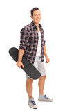 Young man holding a skateboard. Full length portrait of a young man holding a skateboard and looking at the camera isolated on white background Stock Images