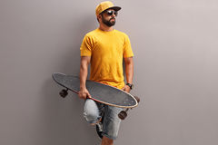 Young man holding a skateboard. In his hand and looking in the distance Royalty Free Stock Photography