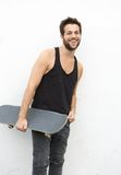 Young man holding skateboard on white background Stock Photography