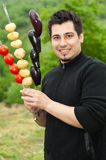 Young man holding skewers with vegetables stock images