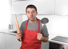 Young man holding skimmer and rolling pin wearing  apron at home Royalty Free Stock Photo