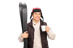 Young man holding skis and drinking hot tea Royalty Free Stock Image