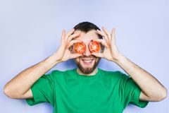 Young man holding slices of red tomatoes in front of his eyes. Young bearded and smiling man holding slices of red tomatoes in front of his eyes. Light purple stock photography