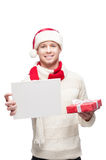 Young man holding small christmas gift and sign. Young casual caucasian man in red santa hat holding small christmas gift and sign with nice toothy smile Stock Photo