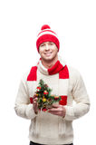Young man holding small christmas tree. Young casual caucasian man in funny red hat holding small christmas tree with nice toothy smile Royalty Free Stock Photo
