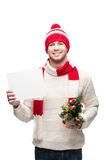 Young man holding small christmas tree and sign. Young casual caucasian man in funny red hat holding small christmas tree and sign with nice toothy smile stock photo