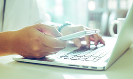 Young man holding smart phone and using laptop . Businessman hand using smart phone and keying the data to laptop,close up Seleted focus Royalty Free Stock Image