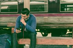 Young man holding smart phone and using music playlist with wait. Ing train at station Stock Photography