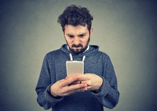 Young man holding smartphone being upset with text message royalty free stock photography
