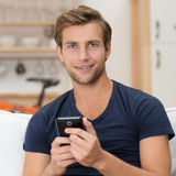 Young man holding a smartphone Stock Photos