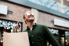 Young man holding smartphone and shopping bags on city street Royalty Free Stock Image