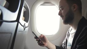 Young man is holding smartphone while sitting in plane indoors. Young man is holding smartphone while sitting in plane indoors stock video
