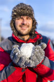 Young man holding a snowball Stock Images