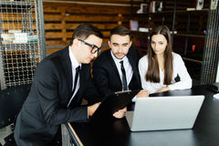 Young man  holding some document and pointing it while sitting together with young couple at the desk in office and ask for signa Royalty Free Stock Image