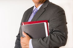 Young man holding some file folders. Man wearing a suit and holding some accounting files Royalty Free Stock Images