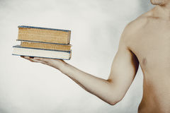 Young man holding stack of books. Royalty Free Stock Image