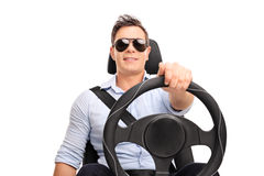 Young man holding a steering wheel driving. Studio shot of a young man holding a steering wheel and pretending to drive isolated on white background Stock Image