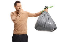 Young man holding stinky garbage bag and covering his nose. Young man holding a stinky garbage bag and covering his nose isolated on white background royalty free stock images