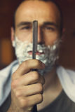 Young man holding straight razor Stock Image