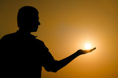 Young man holding the sun on his hand Stock Photos
