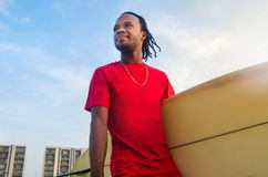 Young man holding a surfboard outdoors. Young African American man holding a surfboard outdoors Stock Photography