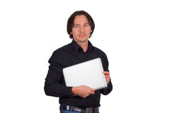 Young man holding a tablet. Handsome young man standing looking at the camera with a serious expression holding a tablet under his arm isolated, upper body Royalty Free Stock Image