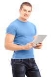 Young man holding a tablet and looking at camera Royalty Free Stock Images
