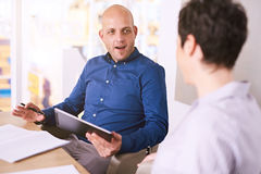 Young man holding tablet during a meeting with business woman Royalty Free Stock Photography