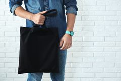 Young man holding textile bag against brick wall, closeup. Mockup for design stock images